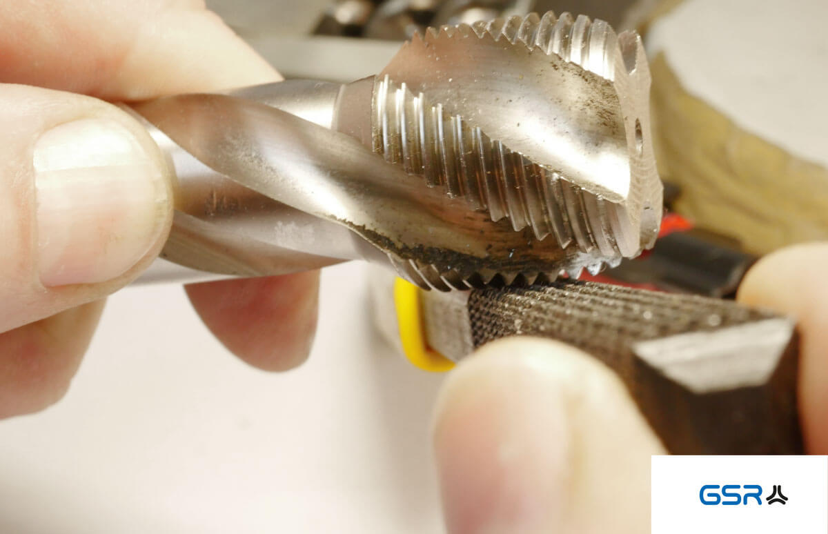 Gewindefeile am Gewindebohrer (Anwendungsbeispiel). Durch leichtes Reiben werden die Gewindegänge frei