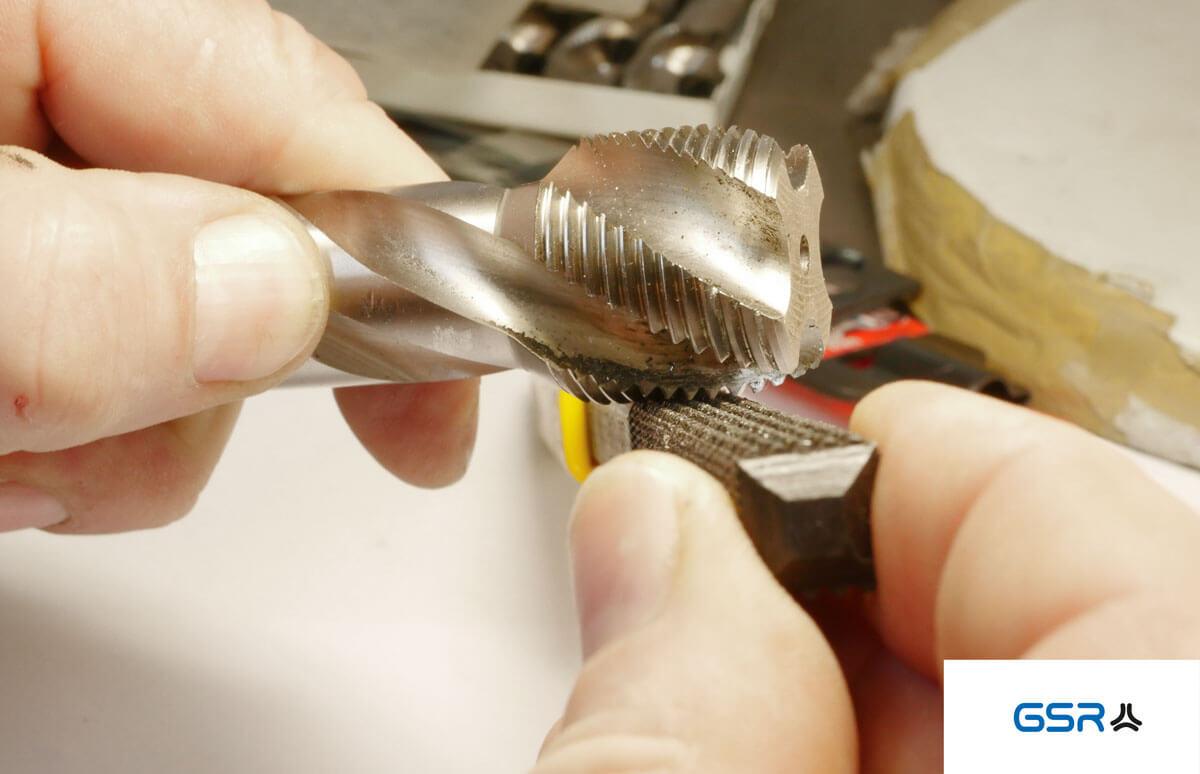 Anwendung der Gewindefeile: durch leichtes hin und her bewegen der Gewindefeile das festgebackene Fremdmaterial abfeilen