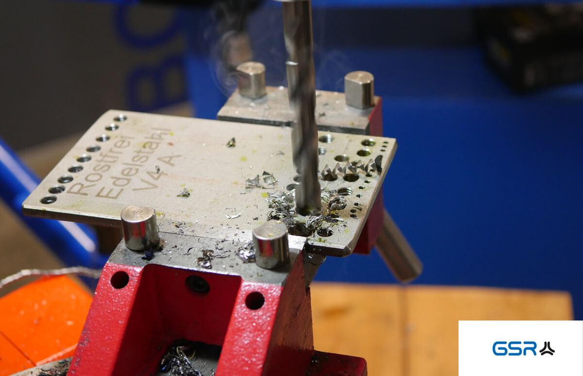 Anleitung Bohren in Metall: Spiralbohrer langsam und gleichmäßig herabsenken um ein Kernloch in die Edelstahlplatte zu erzeugen