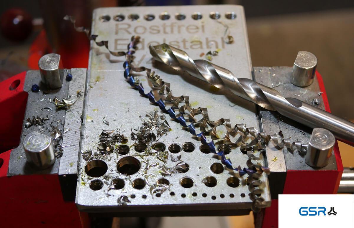 Bohren in Metall: Metall Spiralbohrer (Split Point), Edelstahlplatte mit Bohrlöchern und Metallspäne