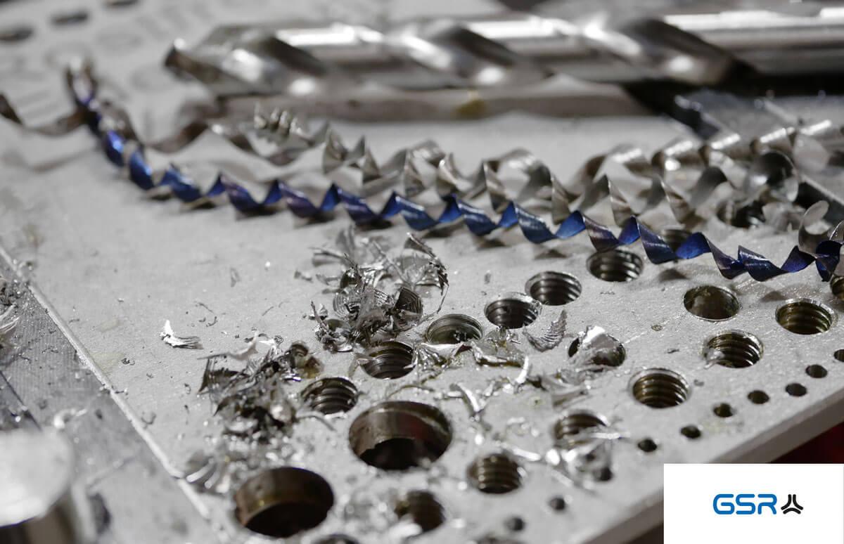 Detailansicht Bohren in Metall: Metall Spiralbohrer mit Split-Point, Edelstahlplatte mit Kernlöchern bzw. Bohrlöcher und Metallspäne