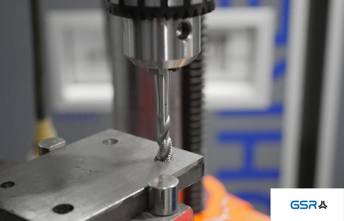 Gewindeherstellung mit einem Maschinengewindebohrer: Der Maschinengewindebohrer ist im Bohrfutter eingespannt und schneidet ins Metallwerkstück
