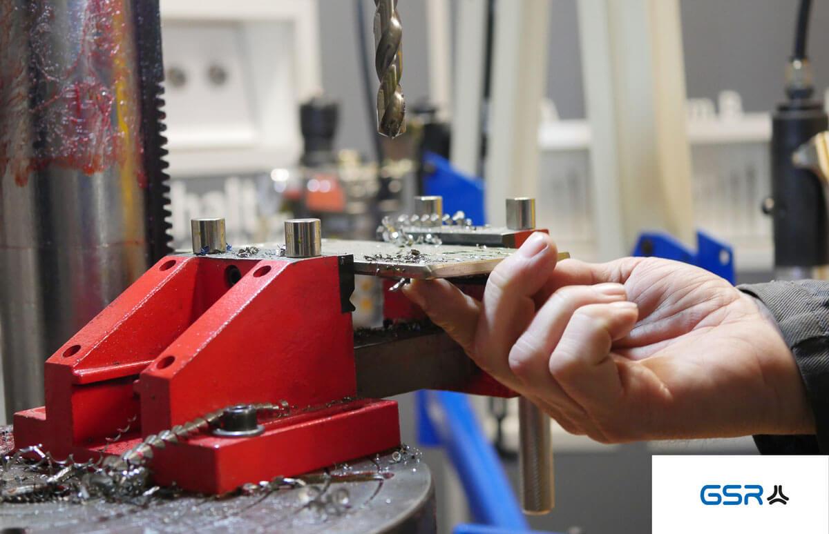 Übersichtsbild Bohren in Metall: Metall Spiralbohrer mit Split Point, Schraubstock und eingespannte Edelstahlplatte. Der Finger zeigt auf das Bohrloch.