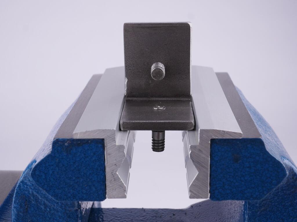 Seitenansicht eines eingespannten Werkstückes zwischen zwei Schonbacken aus Aluminium und Gummi-Profils. Das Werkstück ist im 90 Grad Absatz der Schonbacken eingespannt.