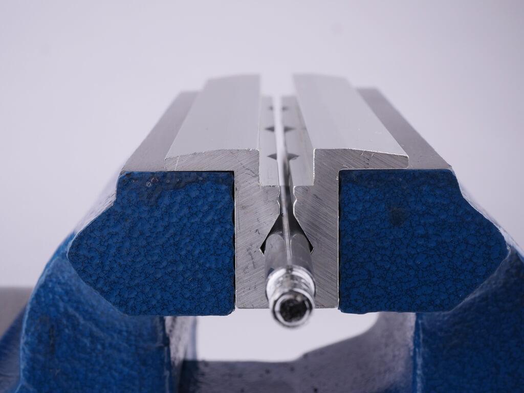 Nahaufnahme des Seitenprofils der Schonbacken aus Aluminium mit Prismenprofil und 90 Grad Absatz eingesapnnt im Schraubstock