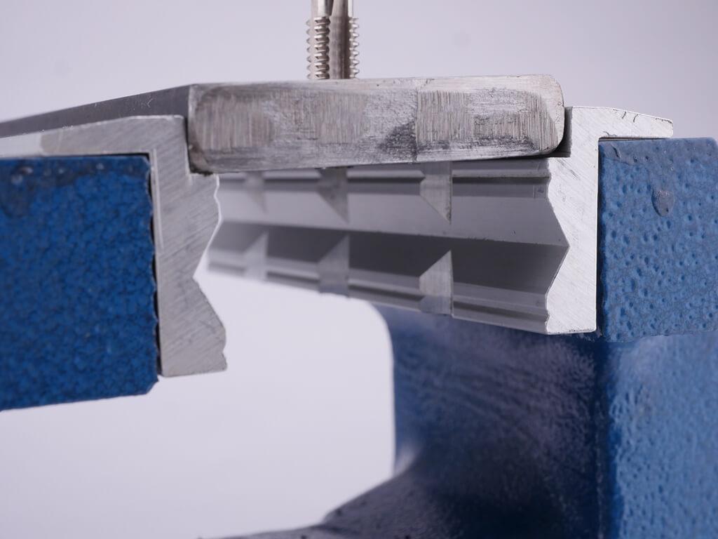 Schonbacken in der praktischen Anwendung: Das werkstück ist zwischen den Schonbacken auf dem 90 Grad Absatz eingespannt, während ein Gewinde geschnitten wird.