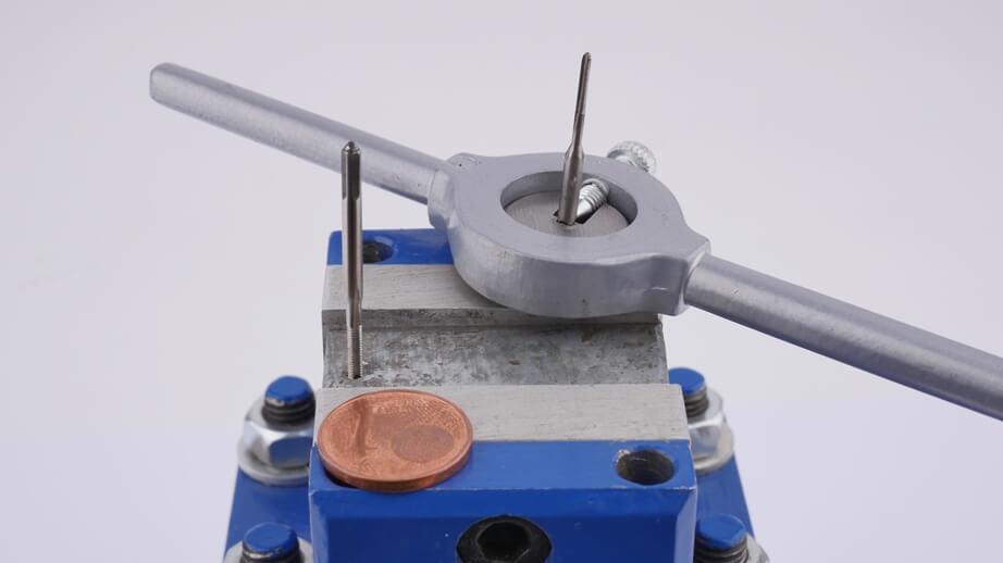 Miniatur-Gewindebohrer Nahaufnahme: Gewindeschneider, Haltewerkzeug, Werkstück und 1-Cent zum Vergleich