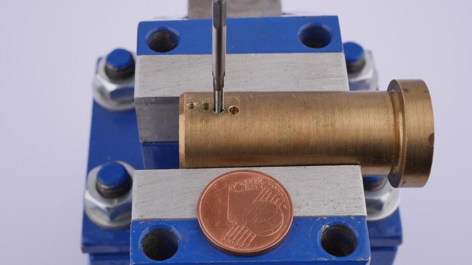 Nahaufnahme: Mit dem Miniatur-Gewindebohrer ein Gewinde in da Rohr schneiden. Das 1 Cent Stück dient zum Vergleich